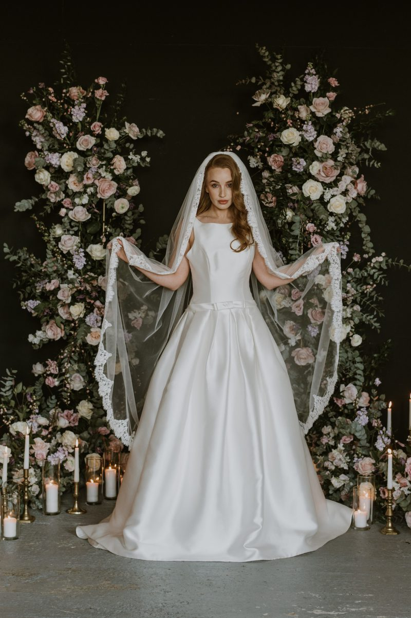 lace wedding veil, models hold the gorgeous lace veil in both hands.