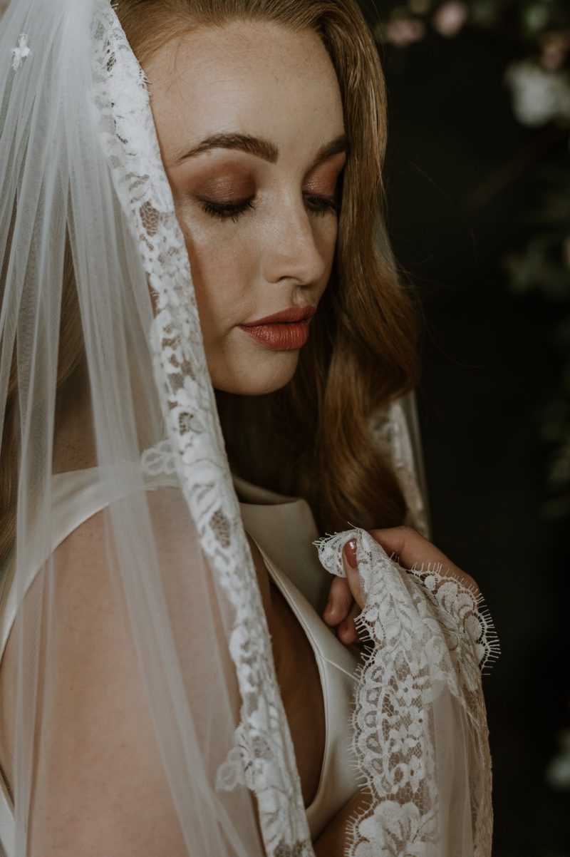 Lace wedding veil, side rose and scalloped detail draped through the models hand.
