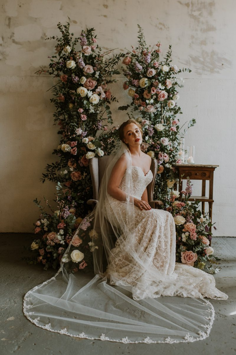 Ivory beaded veil, model wears the Chapel length veil while sitting on a beautiful chair surrounded by flowers.