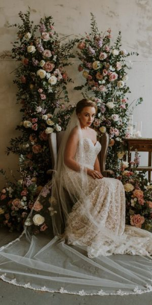 Beaded veil, model wear the Chapel length veil siting on a chair surrounded by flowers .