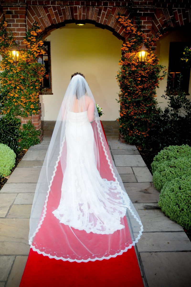 Model wears a lace edged wedding veil