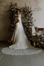 Model wearing ivory long wedding veil with cascading handsewn petals.